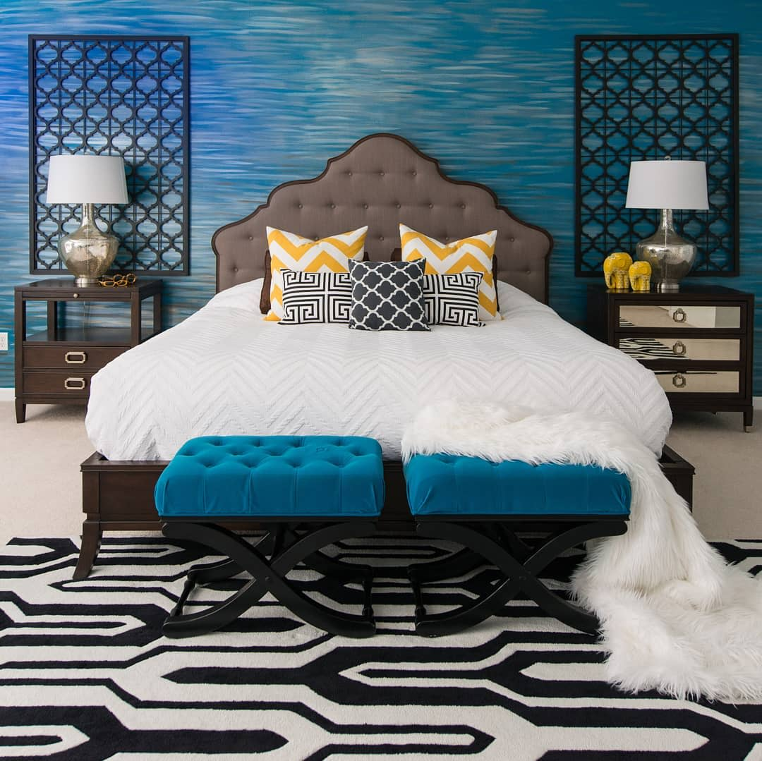 Bedroom Textured Blue Wall Black wall panels Chevron Patterned bed sheets pillows and set of foot stools.