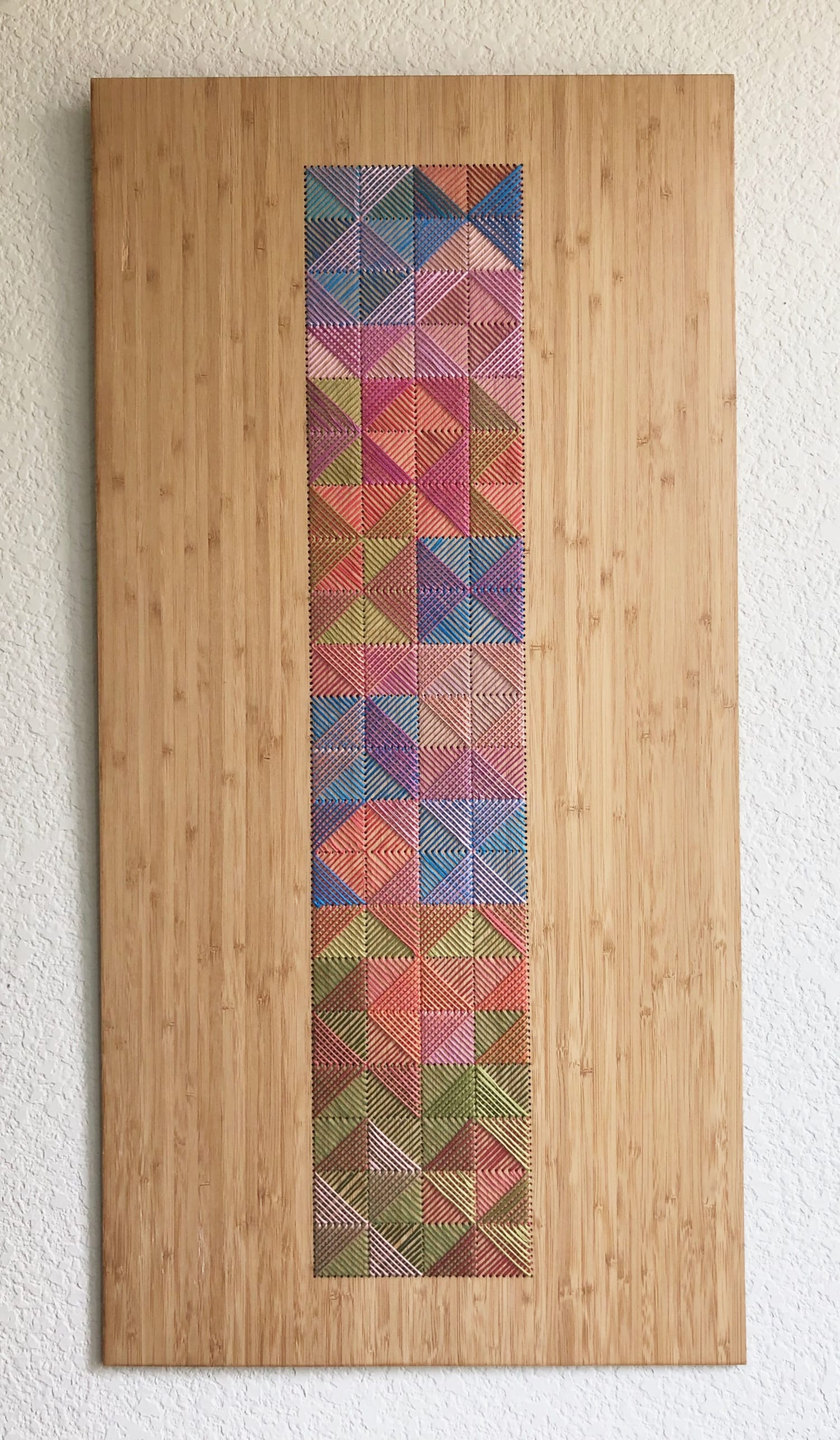 long embroidered wall hanging on wood