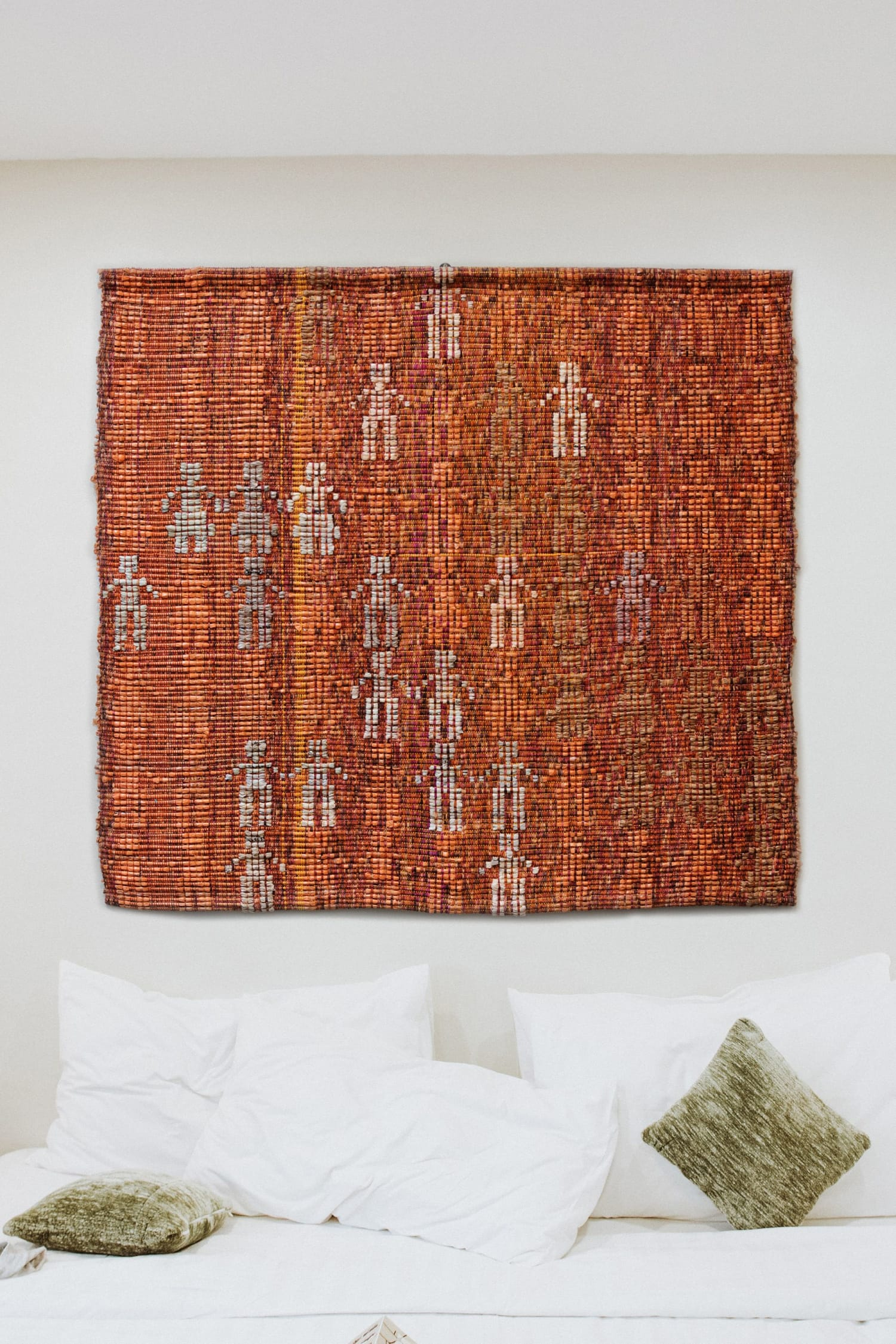 Orange handwoven wall hanging with people