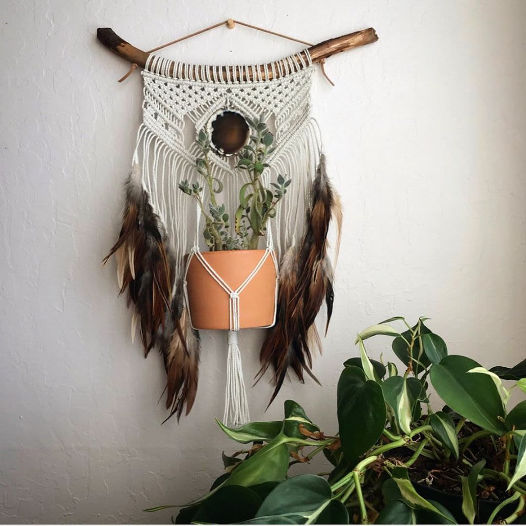Macrame plant hanger with feathers