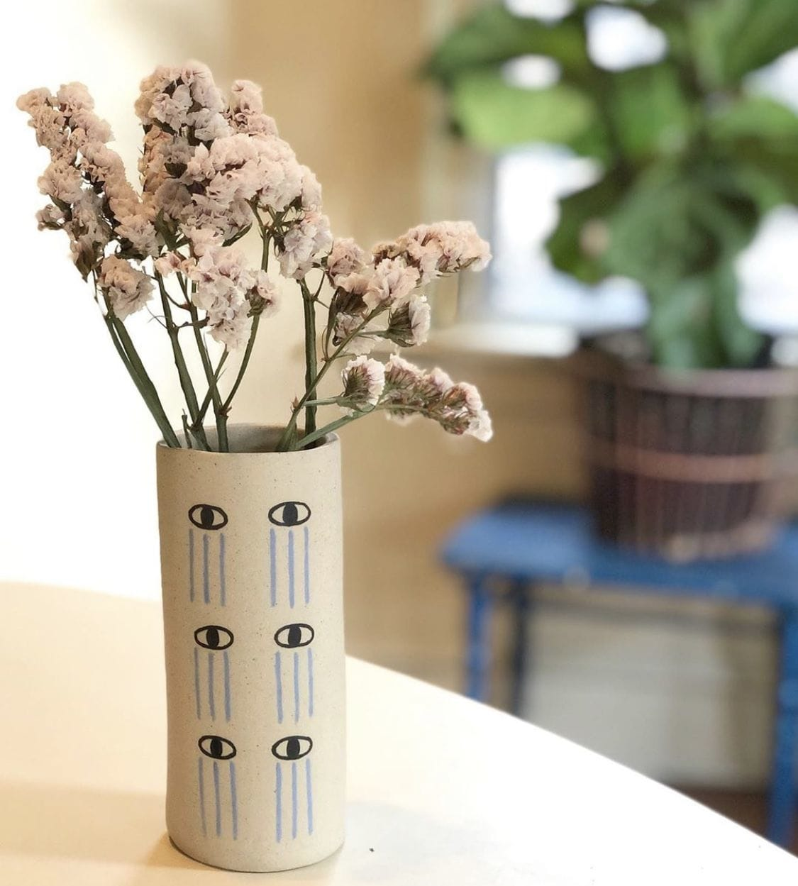 White Cylindrical Vase with Crying Eyes Repeating Pattern