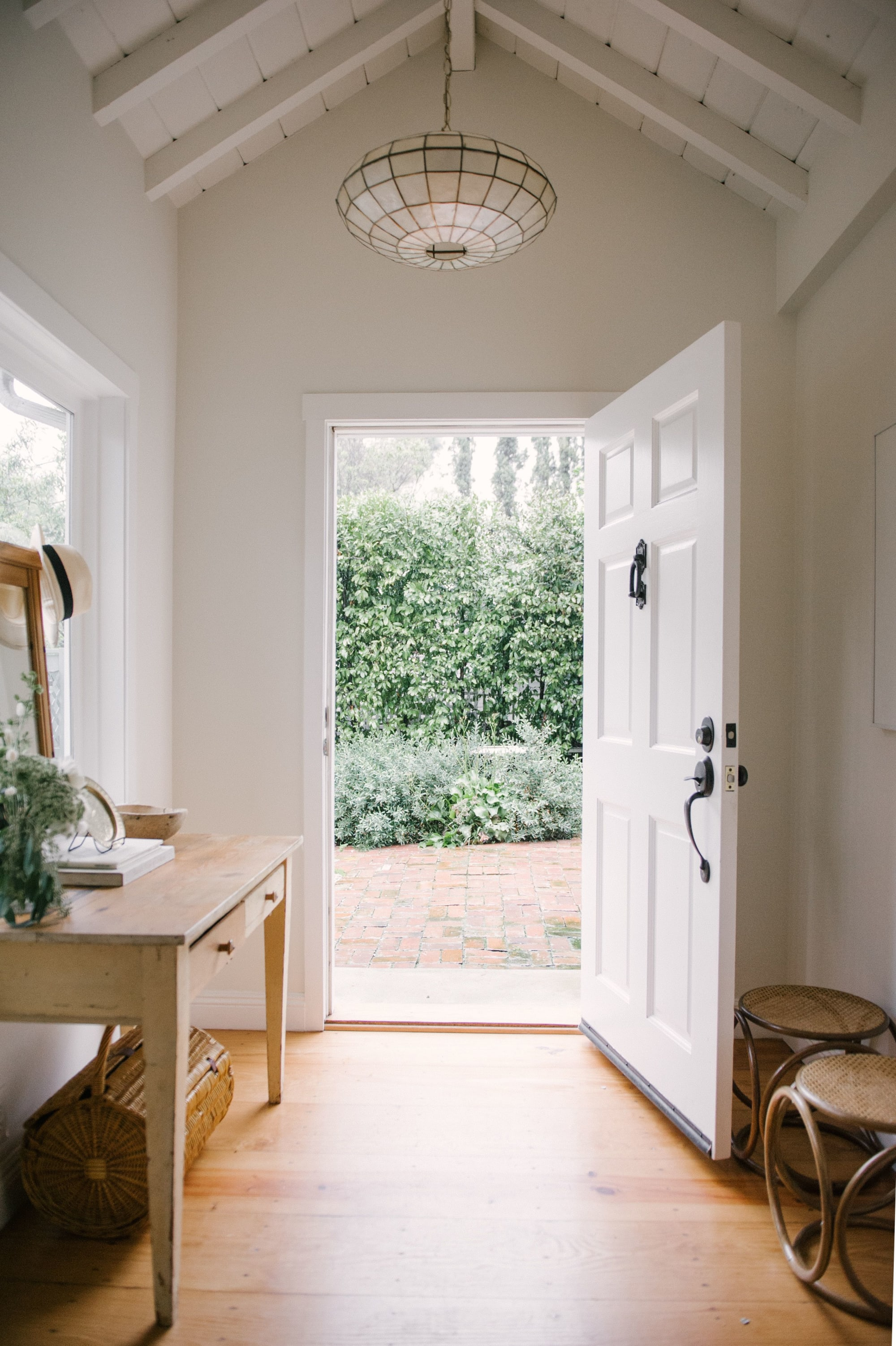 Open white front door, natural wood furniture