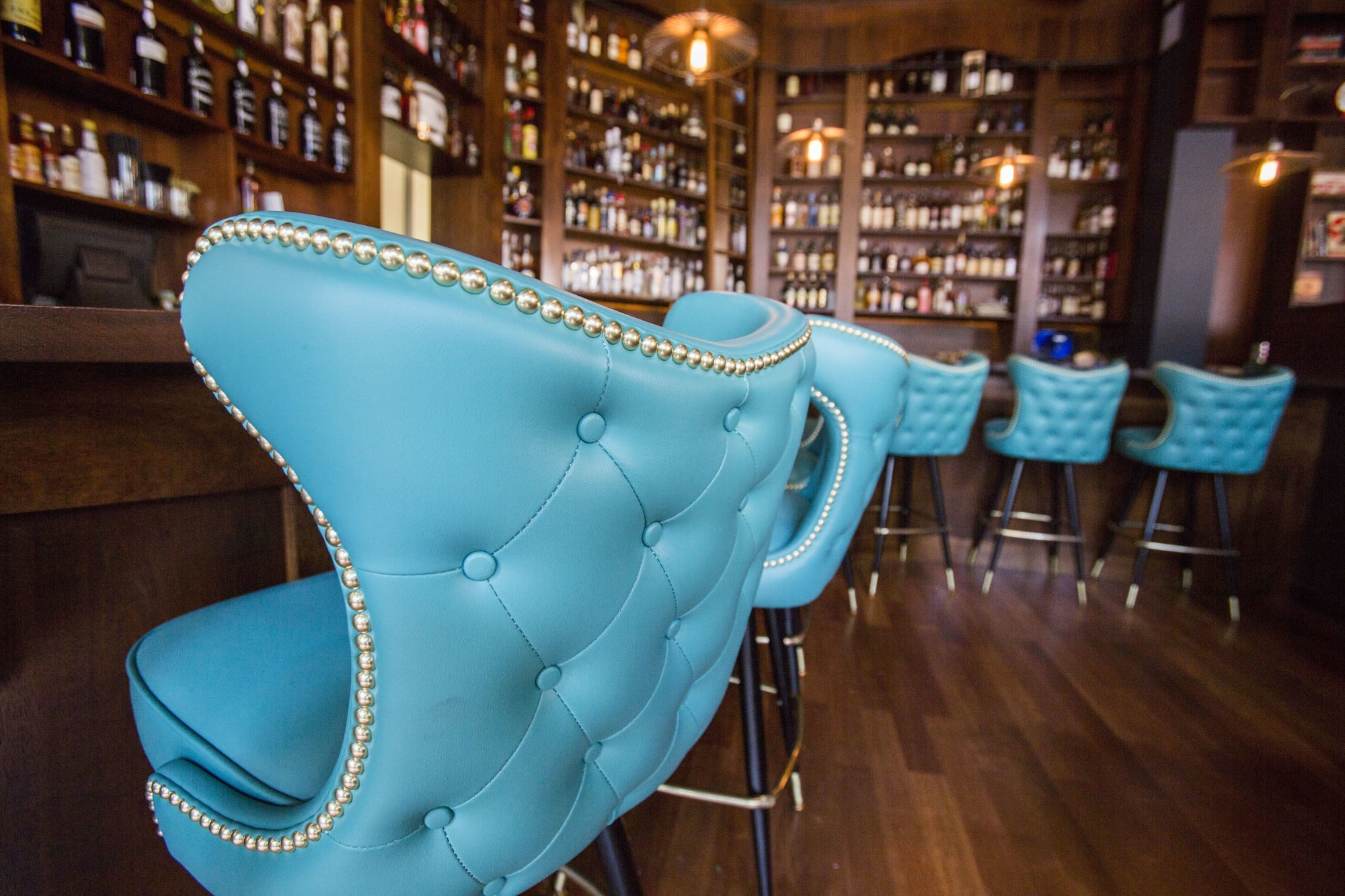 cyan winged button tufted barstool