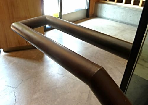 Hardware by Berland Design seen at Roka Akor San Francisco, San Francisco - Custom Made Patina'd Hand Rails