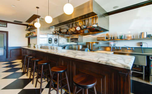 Tables by Estee Stanley seen at Petit Trois, Los Angeles - Carrera Marble-topped Wood Bar