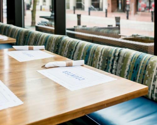 Tables by Melad StudioWorks seen at The Hotel Salem, Salem - Walnut table tops