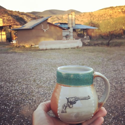Cups by Elemental Artworks - handmade pottery by Rena Hamilton seen at Clarkdale, Clarkdale - Mug with 1873 Peacemaker revolver