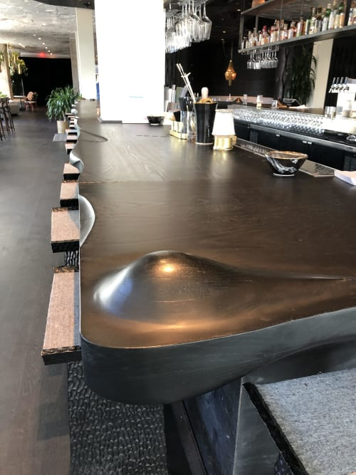 Furniture by Michael Wilson Design seen at The LINE Austin, Austin - Stained Ash Sculpture with Metal Accent (Bar Counter)