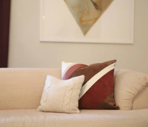 Pillows by Storyteller Studio seen at Private Residence, Louisville - Desert Stripe Leather Throw Pillow and Alpaca Cable Knit Throw Pillow