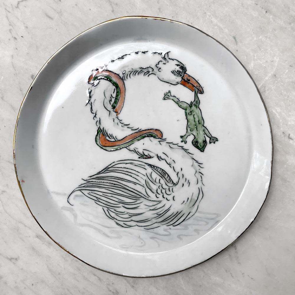 ceramic glossy plate with swan eating frog